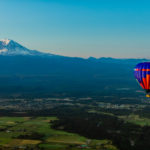 Hot air balloon flying in front of Mt. Rainier
